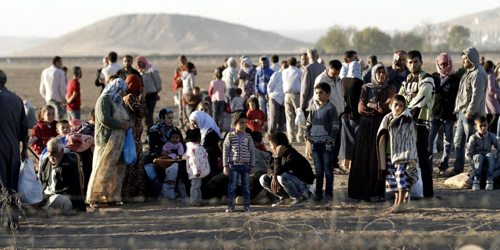 Syrians within a group of refugees wait near the Turkish-Syrian border after fleeing Syria, near Sanliurfa, Turkey, 21 September 2014. Nearly 100,000 Syrian Kurds fleeing the Islamic State militant group have crossed into Turkey in the past three days, a UN official said.  ANSA/ULAS YUNUS TOSUN