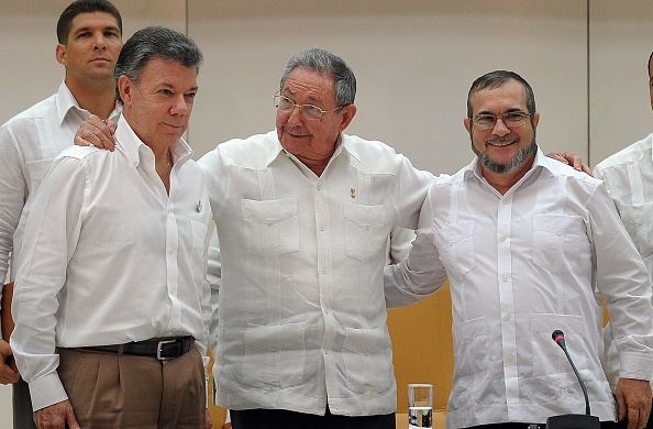 "Cuban President Raul Castro (C) embraces Colombian President Juan Manuel Santos (L) and the head of the FARC guerrilla Timoleon Jimenez, aka Timochenko (R), during a meeting in Havana on September 23, 2015. The Colombian government and FARC rebels announced a key breakthrough in their nearly three-year peace talks Wednesday with the signing of a deal on justice for crimes committed during the five-decade conflict. The deal includes the creation of special courts and a broad amnesty, though this will not cover ""crimes against humanity, serious war crimes"" and other offenses including kidnappings, extrajudicial executions and sexual abuse, said officials from Cuba and Norway, the guarantors in the talks. AFP PHOTO / Yamil Lage (Photo credit should read YAMIL LAGE/AFP/Getty Images)"